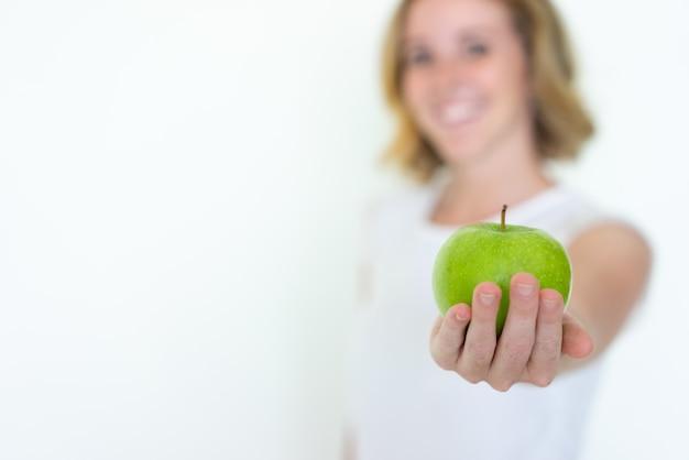 Blurred woman offering ripe green apple Free Photo