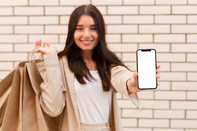Donna vaga che mostra il telefono cellulare dello spazio della copia Foto Gratuite