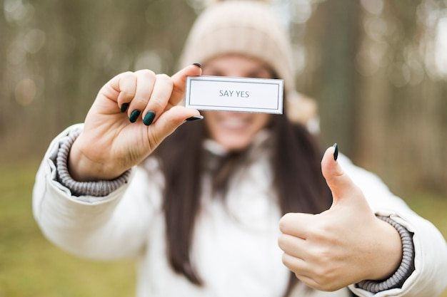 Blurred woman showing inspirational writing and thumb-up gesture Free Photo