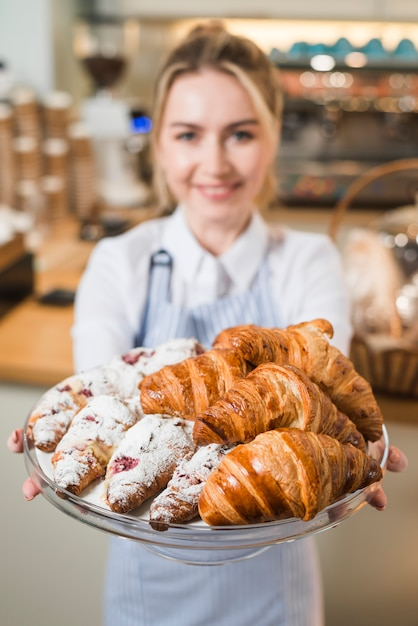 Blurred young woman offering the croissants in the glass cake stand Free Photo