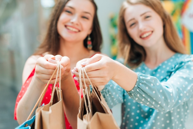 Blurry girls holding shopping bags Free Photo