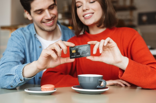 Blurry image of beautiful happy couple man and woman sitting at table in cafe, and holding credit card together Premium Photo