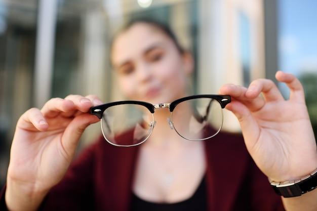 メガネのクローズアップを持つ若い女の子。光学系、blzorukost、遠視、乱視。 Premium写真
