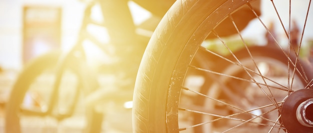 A bmx bike wheel against the backdrop of a blurred street with cycling riders. extreme sports concept Premium Photo