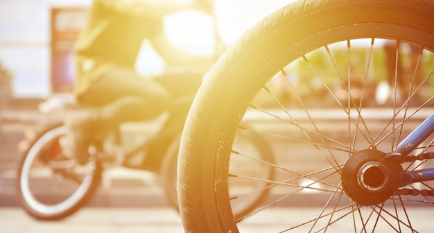 A bmx bike wheel against the backdrop of a blurred street Premium Photo