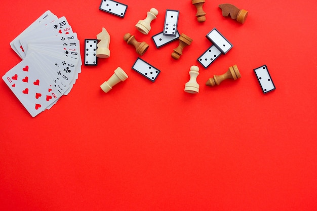 Board games on a red background: playing cards, checkers and chess. the view from the top, place under the text Premium Photo