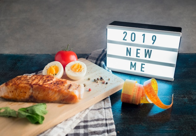 Board with 2019 new me inscription with roasted salmon on table Free Photo
