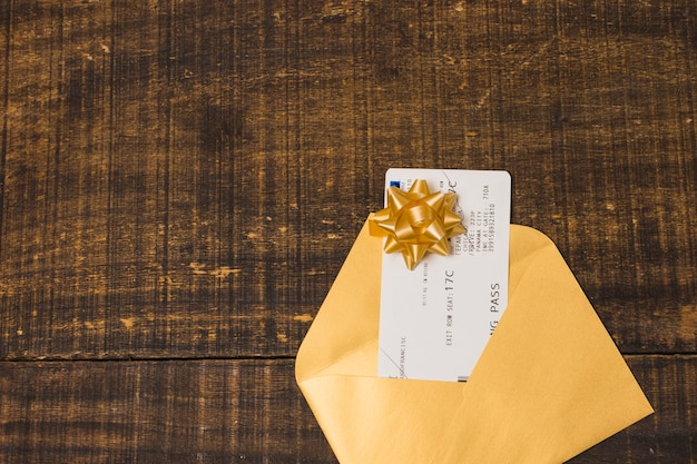 Boarding pass in gift envelope with ribbon bow over textured wallpaper Free Photo