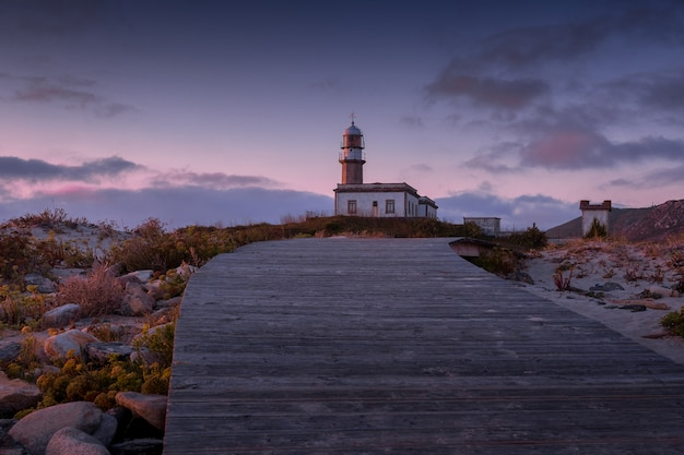 Boardwalk leading to the larino lighthouse during the sunset in the evening in spain Free Photo