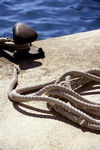 Boat bollard, ropes and knots in mediterranean harbor Premium Photo