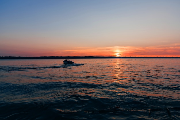 Boat floats on water waves on background of red and blue sunset with sun Premium Photo