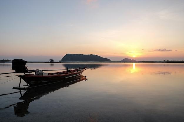 Лодка на берегу моря в окружении холмов с отражением солнца в воде во время заката Бесплатные Фотографии