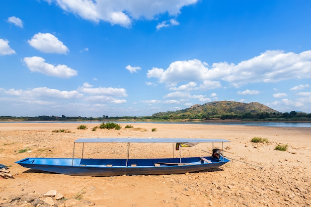 Boat parked in on the dry sand ground of mae khong river with mountain views of laos at the kaeng khud khu rapids at chiang khan Premium Photo