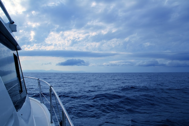 Boat sailing in cloudy stormy day blue ocean Premium Photo