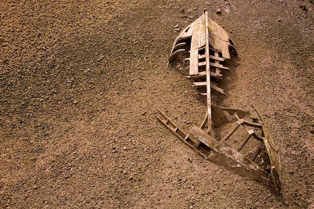 Boat ship skeleton half buried in sand background Premium Photo