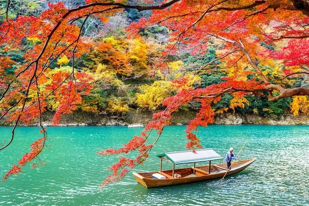 Boatman punting the boat at river. arashiyama in autumn season along the river in kyoto, japan. Free Photo