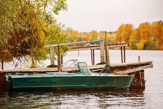 曇り空の午後の秋の桟橋でのボート Premium写真