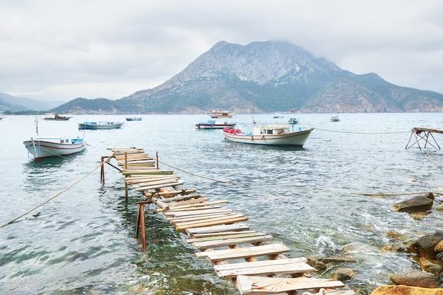 Лодки у разбитого пирса заходят в спокойную голубую морскую воду. Бесплатные Фотографии