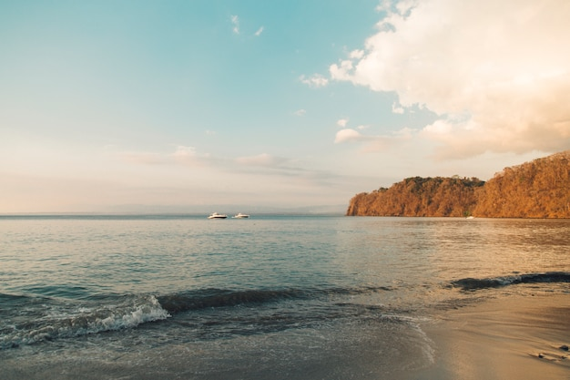 Boats sailing at coastal hills in evening light in sea background Free Photo