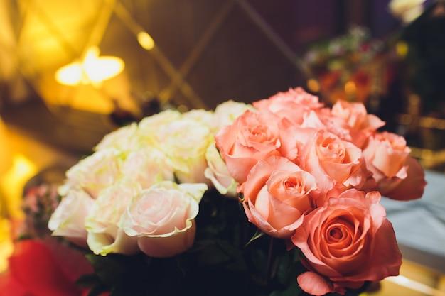 柔らかい色のバラの美しい花束のクローズアップ。 bockehの背景、聴覚障害者のレストラン。浅い焦点深度。あなたのためのコンセプトフラワー。 Premium写真