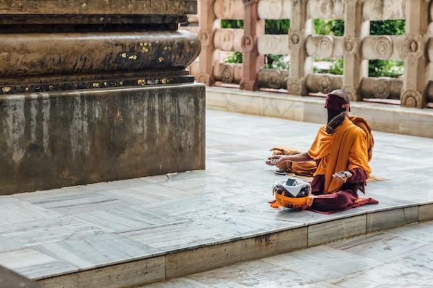 インドのビハール州のbodh gayaで雨が降っている間mahabodhi寺院の近くのbodhiの木の近くの瞑想のインド仏教の僧侶。 Premium写真