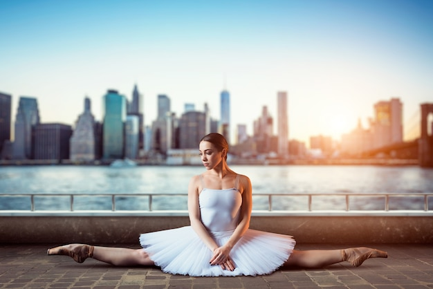 Гибкость тела артиста классического балета. балерина в белом платье сидит на шпагате, вид спереди, городской пейзаж с небоскребами Premium Фотографии