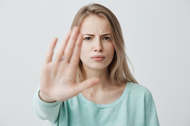 Body language. disgusted stressed out angry blonde young female with straight fair hair posing against wall, keeping hand in stop gesture, trying to defend herself as if saying: stay away from Free Photo