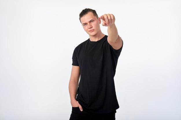 ボディランゲージ。ハンサムな若い自信を持って男があなたを指しています。私はあなたを選びます。私はあなたが欲しいです。 Premium写真