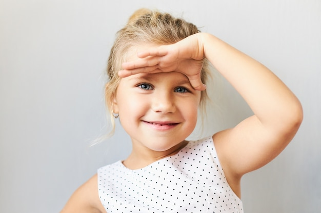 Body language. horizontal shot of cute cheerful little girl with gathered fair hair holding palm on her forehead as if looking into distance, trying to see something far away, smiling happily Free Photo