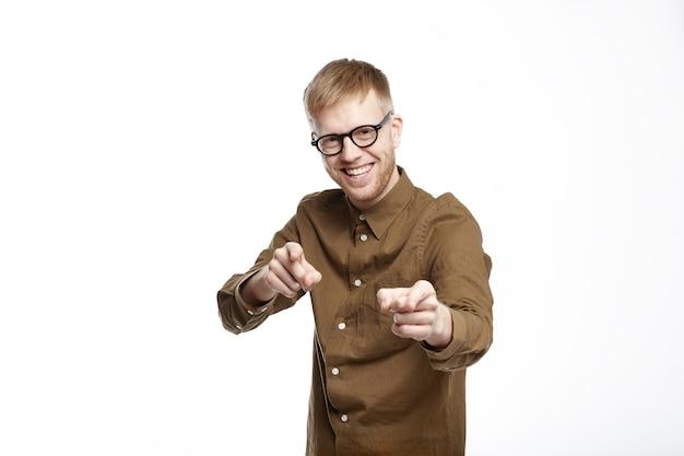 Linguaggio del corpo. inquadratura orizzontale del giovane barbuto felicissimo in camicia alla moda e occhiali ridendo e indicando il visualizzatore Foto Gratuite