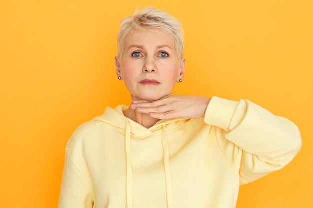 Язык тела. горизонтальное студийное изображение разочарованной сердитой пенсионерки в стильной толстовке с капюшоном, держащей ладонь на шее, угрожающей жестом и недовольной усталым взглядом Бесплатные Фотографии