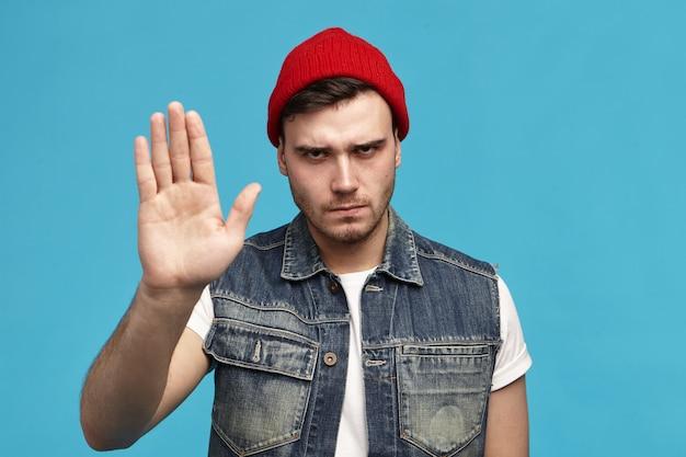 Язык тела. изолированный снимок модного стильного молодого человека в красной шляпе, показывающего отрицательную реакцию Бесплатные Фотографии