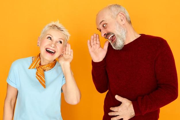 Linguaggio del corpo. ritratto di due pensionati caucasici anziani divertenti con problemi di udito che hanno conversazione, tenendo le mani all'orecchio e gridando ma non riescono a distinguere le parole. concetto di sordità Foto Gratuite