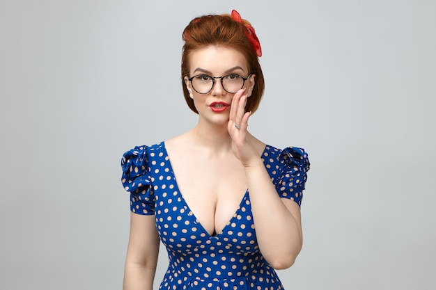 Body language. pretty young european woman wearing glasses, elegant dress and bright make up holding hand at her mouth, sharing top secret or confidential information with you, having mysterious look Free Photo