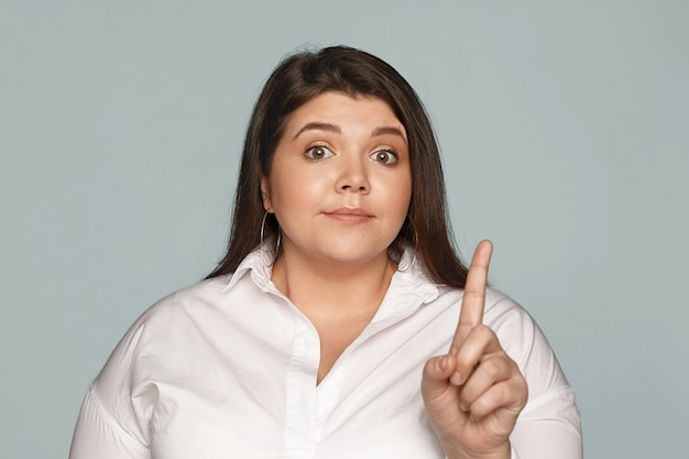 Body language. strict attractive young overweight female ceo with chubby cheeks raising eyebrows being displeased with ineffective work results, reprimanding employees, shaking index finger Free Photo