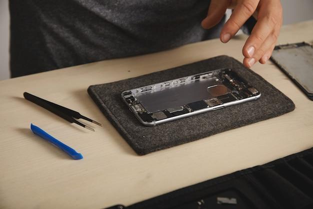 分解されたスマートフォンの本体、取り外したリチウムイオン電池で洗浄され、新しい部品を組み立てて取り付ける準備ができています 無料写真