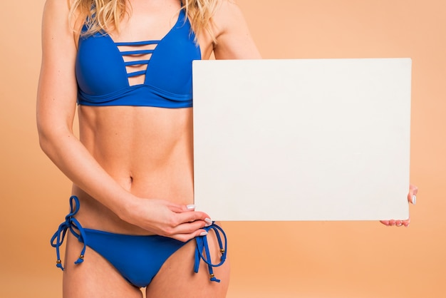 Body part of young woman in blue swimsuit with blank paper Free Photo