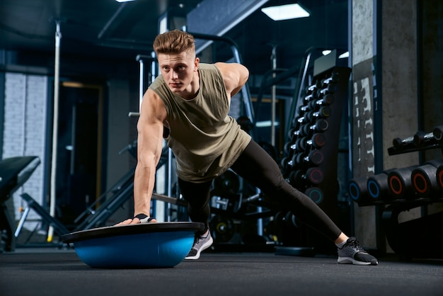 Bodybuilder doing push ups on one hand. Free Photo