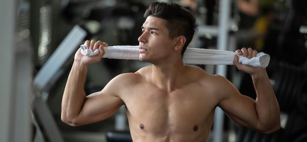 Человек культуриста ослабляет после поднимать весы в спортзале спорта, конец вверх. Premium Фотографии