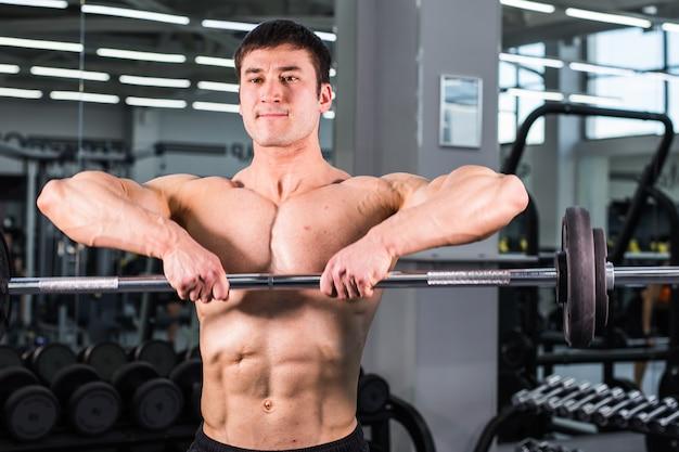 체육관에서 완벽한 팔뚝, 삼두근 및 가슴을 가진 보디 빌딩 남자 프리미엄 사진