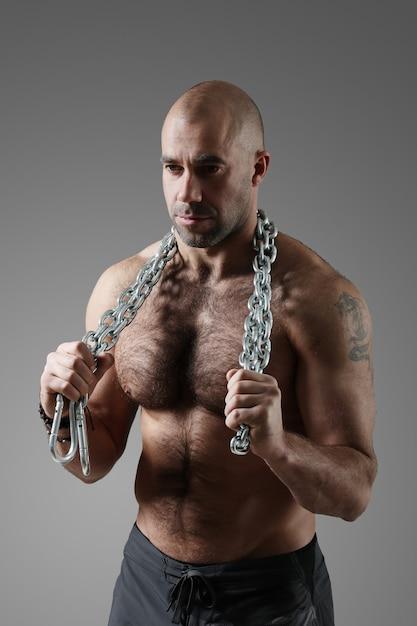 Bodybuilder in posa e mostrando i muscoli Foto Gratuite