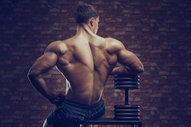 Bodybuilder strong man pumping up back muscles Premium Photo