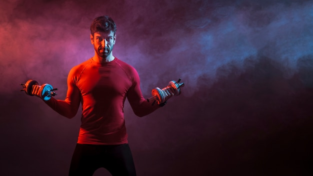 Bodybuilder with weights in studio Free Photo