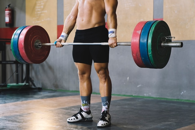 Bodybuilding concept with man holding barbell Free Photo