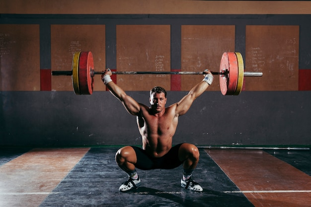 Bodybuilding in gym with strong man Free Photo