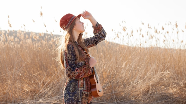 Bohemian woman in the field holding ukulele Free Photo