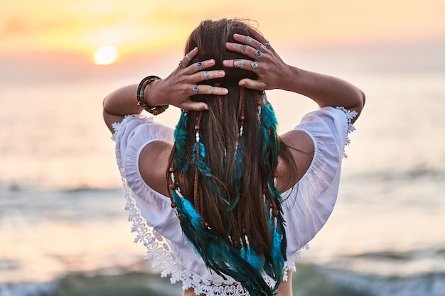 Boho hippie woman with blue feathers in hair Premium Photo