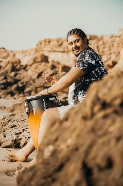 Boho musucian на заброшенном пляже со своим барабаном Бесплатные Фотографии