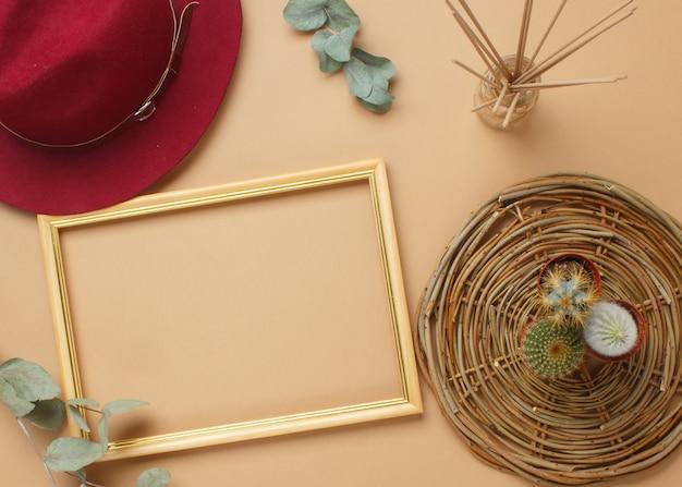 Современный рабочий стол в стиле бохо с рамой, сочными, шляпкой, ароматическими палочками, салфетками. Premium Фотографии