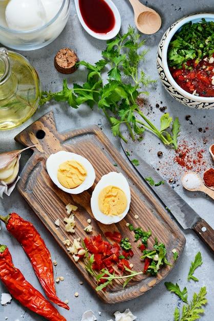 ゆで鶏卵。ゆでた卵のマリネを野菜、ハーブ、スパイス、トマトソースで調理するプロセス。 Premium写真
